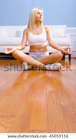 Young woman sitting cross legged on floor with hands on knees meditating. Vertical shot. - stock photo