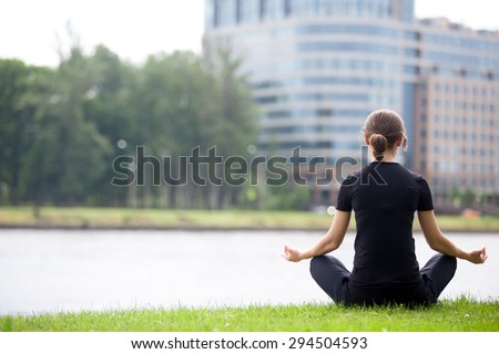 Young woman sitting cross legged on river bank in front of modern office building, meditating, practicing yoga Easy Pose, Sukhasana, asana for meditation, pranayama, breathing, back view, copy space - stock photo