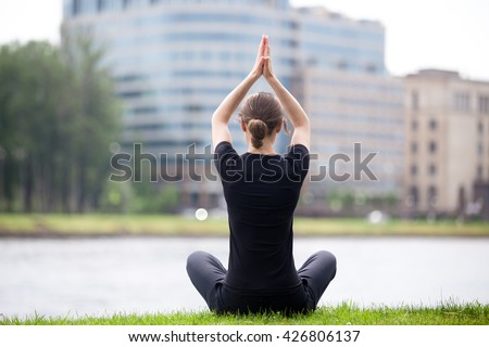 Young woman sitting cross legged on riverbank in front of blue glass modern office building, practicing yoga Easy Pose, Sukhasana, posture for meditation, pranayama, breathing, full length, back view - stock photo