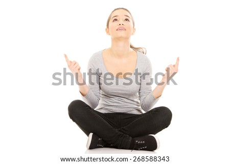 Young woman sitting cross legged pointing up. - stock photo