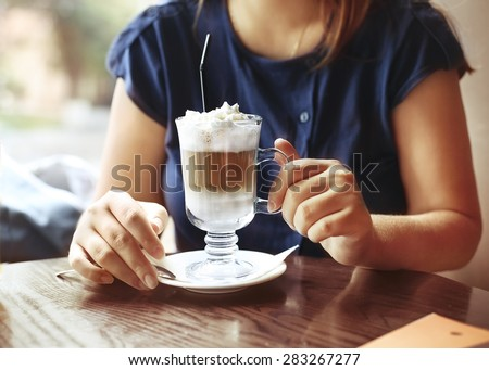 Young woman sitting in a cafe with a cup of coffee latte. Close up - stock photo