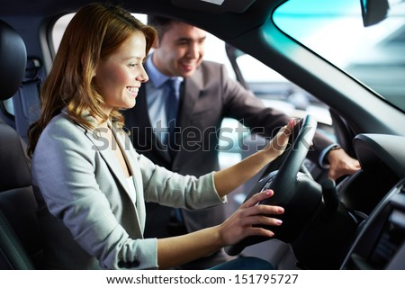 Young woman sitting in a car enjoying its comfortable compartment - stock photo