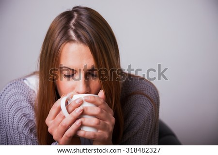 Young woman sitting in a chair drinking a hot cup of maybe tea, coffee, hot chocolate or soup, with her eyes closed. - stock photo