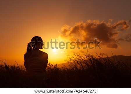 Young woman sitting in a field watching the sunset.  - stock photo