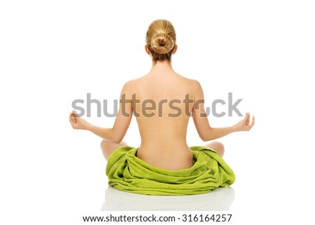 Young woman sitting in a yoga position covered with green towel - stock photo