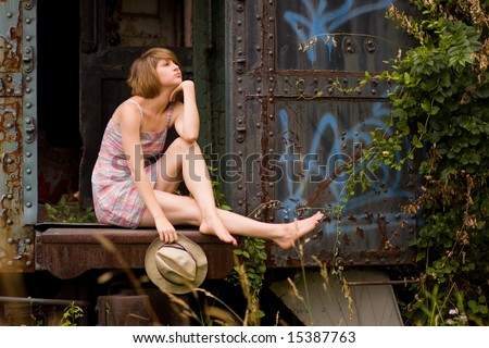Young woman sitting in an abandoned train car. - stock photo