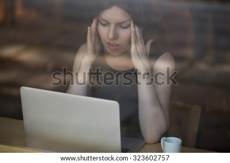 Young woman sitting in cafe in front of laptop, looking at screen with frustrated expression, holding her head in hands, having headache, low or high arterial blood pressure, stress - stock photo