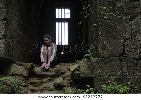 Young woman sitting in dungeon of old castle in Brittany - stock photo