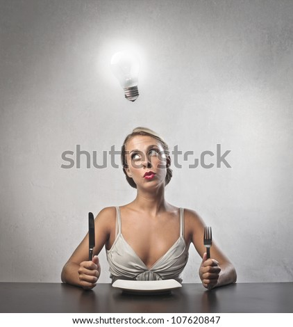Young woman sitting in front of a dish at lunchtime with light bulb over her head - stock photo