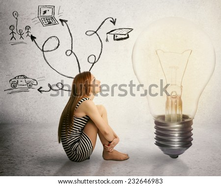 Young woman sitting in front of light bulb thinking has many thoughts life ideas isolated on grey wall background. Human face expression motivation perception vision, brain power, imagination concept  - stock photo