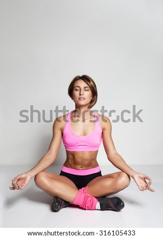 Young woman sitting in lotus position on the gray background - stock photo