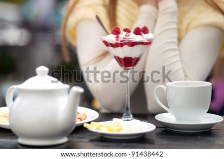 young woman sitting in outdoor cafe tasting dessert - stock photo
