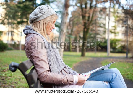 Young woman sitting in park and reading magazine - stock photo
