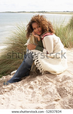 Young Woman Sitting In Sand Dunes Wrapped In Blanket - stock photo