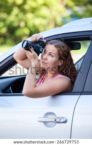 Young woman sitting in the car and take pictures with a digital camera from the window - stock photo