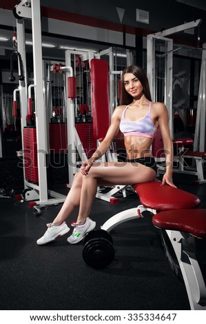 Young woman sitting in the gym. Female fitness girl exercising indoor in fitness center. Beautiful fit mixed race Asian Caucasian model. - stock photo