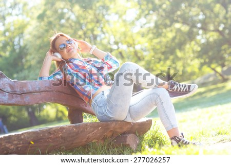Young woman sitting in the park and listening to music - stock photo