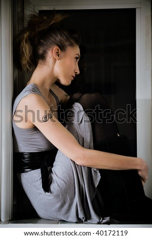 young woman sitting in window frame, indoor shot - stock photo