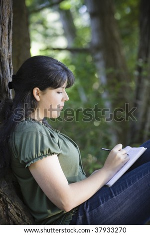 Young Woman Sitting in Woods Writing in Journal - stock photo