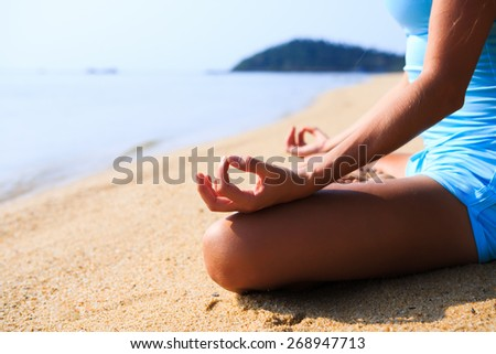 Young woman sitting in yoga pose lotus and making meditation on the beach - stock photo