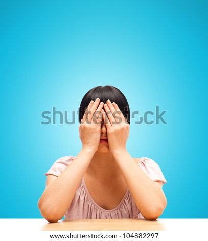 Young woman sitting isolated against blue background with eyes closed by her hands - stock photo