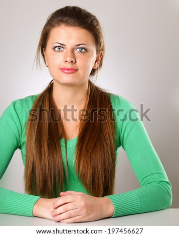 young woman sitting isolated on grey background - stock photo