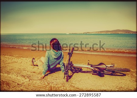 Young woman sitting near a bicycle on beach in summer. Image with vintage color effect and rectangular frame - stock photo
