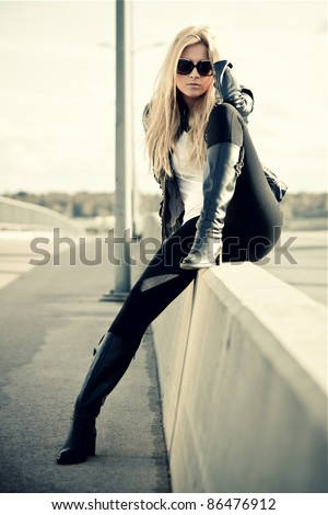 Young woman sitting near a highway - stock photo