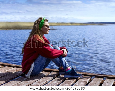Young woman sitting near the lake on a wooden pier in sunny day - stock photo