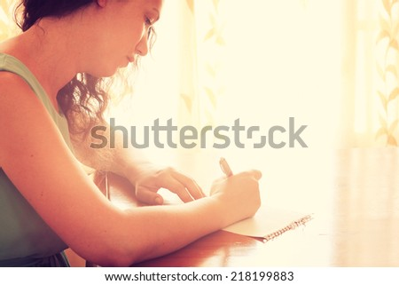young woman sitting near window and writing. retro filtered image. photograph with natural window light  - stock photo