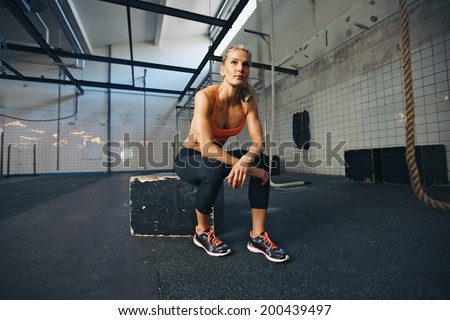 Young woman sitting on a box at crossfit gym looking away. Fit young caucasian female athlete at gym. - stock photo