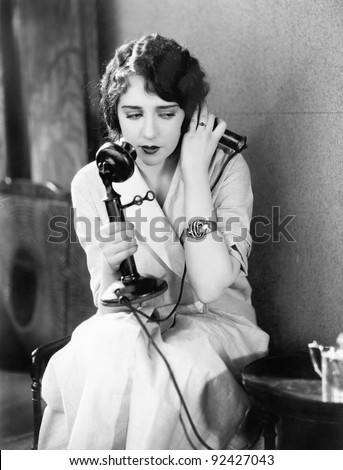 Young woman sitting on a chair holding a telephone - stock photo
