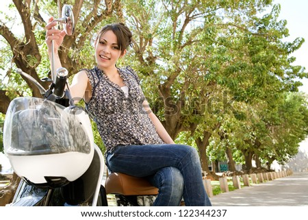 Young woman sitting on a classic motorbike while visiting a small city destination on vacations, smiling at the camera with trees aligned behind her. - stock photo