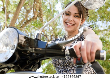 Young woman sitting on a classic motorbike while visiting a small city destination on vacations, smiling at the camera with trees behind her. - stock photo