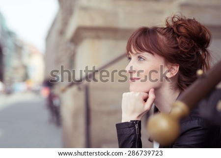 Young woman sitting on a flight of steps in an urban street with her chin on her hands staring thoughtfully ahead, side view - stock photo