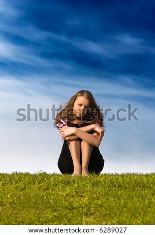 Young woman sitting on a grass. - stock photo