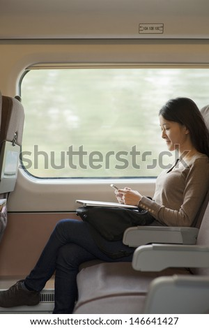Young woman sitting on a train using her phone - stock photo