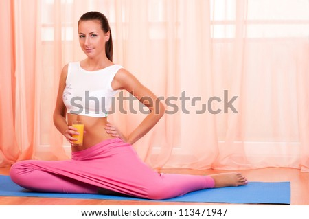 Young woman sitting on a yoga mat and holding glass of orange juice - stock photo