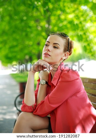 Young woman sitting on bench in green park, thoughtfully looking away - stock photo