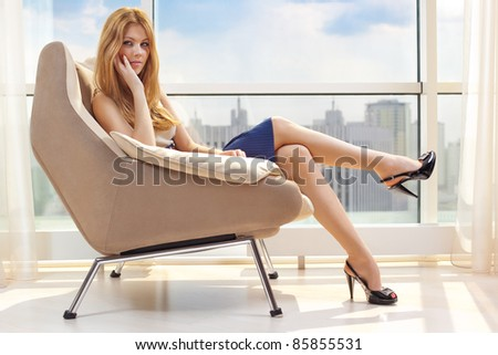 Young woman sitting on chair on window background. - stock photo