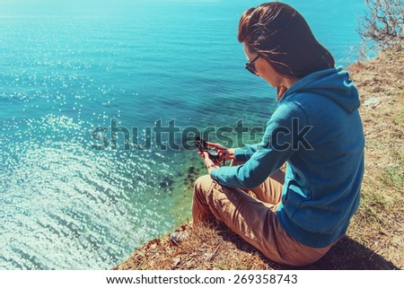 Young woman sitting on coast near the sea and searching direction with a compass. Focus on compass. - stock photo