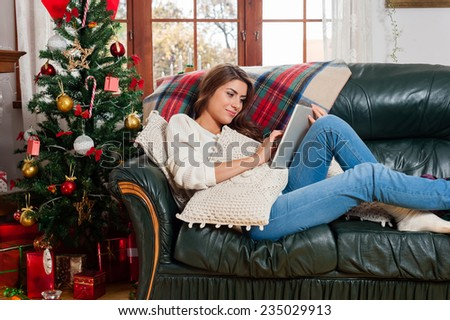 Young woman sitting on couch, alone, in front of christmas tree on living room,using tablet pc. - stock photo