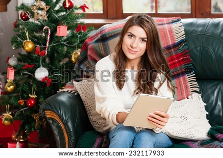 Young woman sitting on couch, alone,over christmas tree background on living room,showing a tablet - stock photo