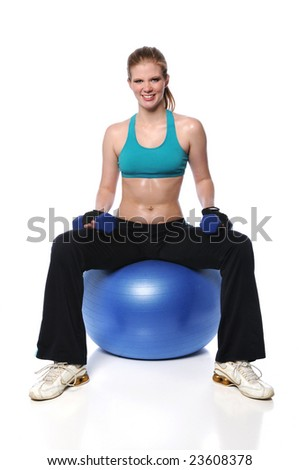 Young woman sitting on exercise ball holding dumbbells - stock photo