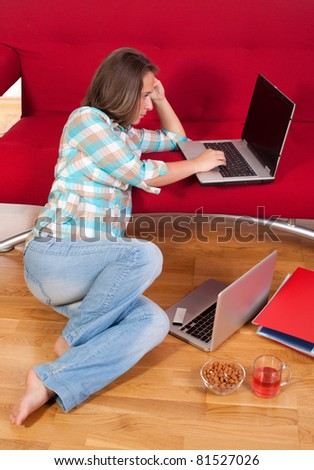 young woman sitting on floor at home in living room using her laptop - stock photo