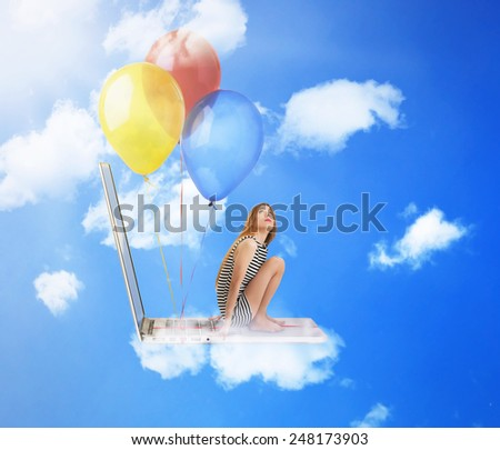 Young woman sitting on laptop computer with fun colorful balloons flying high in blue sky - stock photo