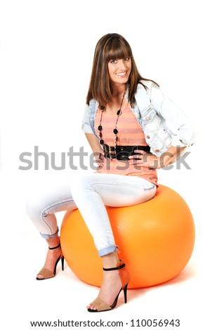 Young woman sitting on orange pilates ball. - stock photo