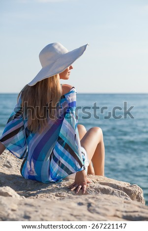 Young woman sitting on rock and enjoying sun  - stock photo