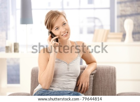 Young woman sitting on sofa at home, talking on mobile phone, smiling.? - stock photo