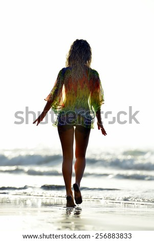 young woman sitting on the beach in summer vacation - stock photo